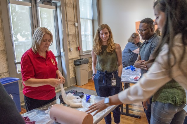 "Gina Pickard, Trauma Division manager at Brooke Army Medical Center's Trauma Clinic, shows City of San Antonio council staff members how to pack a wound during Stop the Bleed held at the Plaza de Armas building in Downtown San Antonio Aug. 29, 2019. The training consisted of a presentation where attendees learned the ""ABCs of Bleeding Control"" along with some hands-on practice in applying tourniquets, packing wounds and applying direct pressure to stop bleeding."