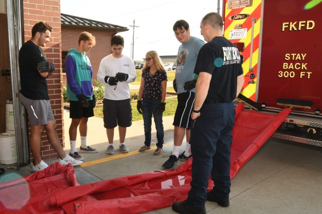 Fort Knox firefighter Jorge Sanchez teaches students from Fort Knox's Junior Firefighter's Program (from left) Tanner Bellamy, Travis Haley, Todd Williamson, Koral Tepley and Buddy Daley) how to direct water through an area so as to minimize water damage to the structure.