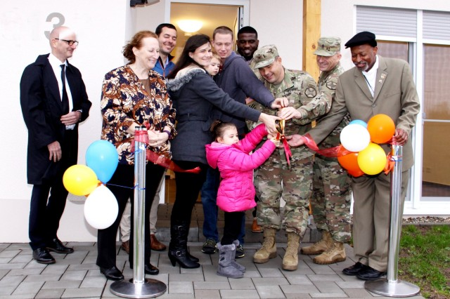 U.S. Army Garrison Rheinland-Pfalz Commander Col. Jason Edwards and Command Sgt. Maj. Brett Waterhouse opened the first new townhome in Baumholder, Germany, with a ribbon cutting Dec. 7, 2018, joined by the Gilbert family --  the first family to move in. (U.S. Army Photo by Bernd Mai)