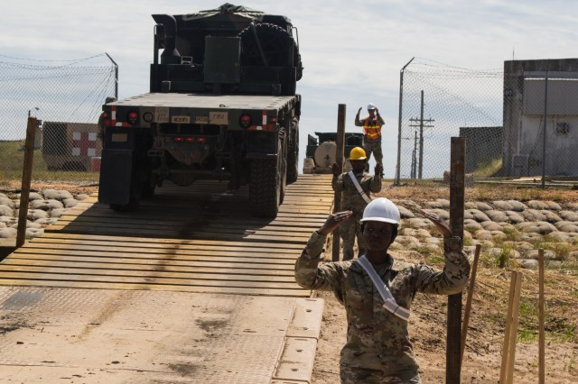 U.S. Army Soldiers assigned to Task Force 11, 7th Transportation Brigade (Expeditionary), ground guide a Heavy Expanded Mobility Tactical Truck off of U.S. Army Vessel New Orleans, Landing Craft Utility 2031, at Singing River Island, Mississippi during a Joint Readiness exercise Sept. 14, 2019. This JRE allowed commanders at several echelons and locations to train in the process of detailed planning and coordination required to move units overseas on a condensed notification and deployment timeline. (U.S. Army Photo by Pfc. Joshua Cowden / 22nd Mobile Public Affairs Detachment)