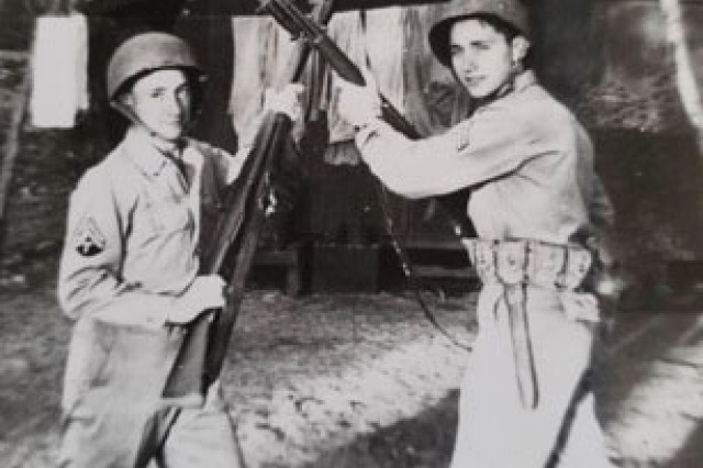 Brothers Ed and Ted Sikora, both Army service members, pose for a photo with their rifles crossed at Pearl Harbor, Hawaii.