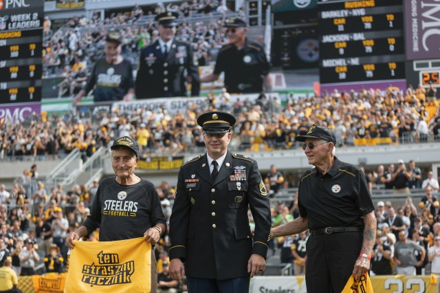 "Theodore ""Ted"" Sikora, left, and Edward ""Ed"" Sikora, right. are honored by the Pittsburgh Steelers with the ATI Salute to Heroes Award at Heinz Field in Pittsburgh, Sept. 15, 2019. The brothers are veterans of World War II. With them is Ted's grandson-in-law, Army Sgt. 1st Class Daniel Vollstedt, center."