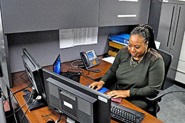 Maintaining a clean work space, like the Army civilian pictured here, helps protect sensitive information.