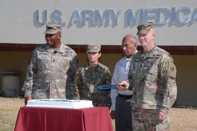 """To celebrate the Redesignation to U.S. Army Medical Center of Excellence, or MEDCoE, the command also conducted a cake cutting ceremony. Assisting MG Sargent and CSM O'Neal were the most junior and most senior personnel in the command as is a time honored military tradition. Instead of a sabre, MEDCoE cut their ceremonial cake with  a replica of the Hospital Corps Knife which was established in 1887. Pictured from left to right: Maj. Gen. Patrick D. Sargent, Pvt. 1st Class Briana Castilleja Hernandez, Mr. Jesus Serbantez, and Cmd. Sgt. Maj. William """"Buck"""" O'Neal."""