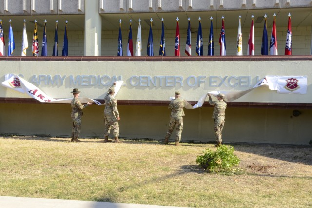 """MEDCoE command team Maj. Gen. Patrick D. Sargent and Cmd. Sgt. Maj. William """"Buck"""" O'Neal were assisted in unveiling the new name by Senior Drill Sergeant Kyle Specht (far left) and Staff Sergeant Alexander Bach, the center's 2019 Best Warrior winner (far right)."""