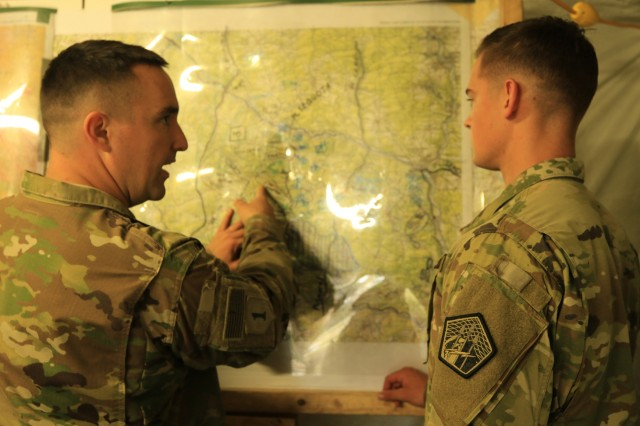 2nd Lt. Shane Neal receives guidance from Cpt. Douglas Gain, officers with the Cyber and Electromagnetic Activities Team, as they review their plans during Exercise Saber Junction 2019 (SJ19) at the Grafenwoehr Training Area, Germany, Sept. 12, 2019. SJ19 is an exercise involving nearly 5,400 participants from 16 ally and partner nations at the U.S. Army's Grafenwoehr and Hohenfels Training Areas, Sept. 3 to 30 Sept. 2019. SJ19 is designed to assess the readiness of the U.S. Army's 173rd Infantry Airborne Brigade to execute land operations in a joint, combined environment and to promote interoperability with participating allies and partner nations. (U.S. Army Photo by Spc. Joseph Knoch)