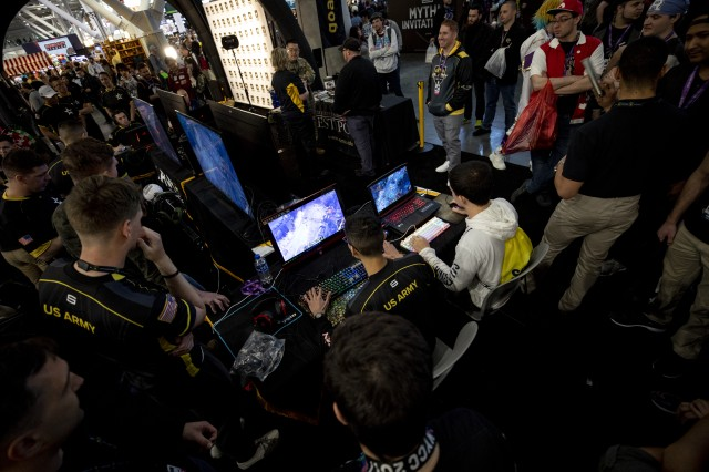 People gather around the U.S. Army exhibit to watch the Army's newly founded Esports team play video games while attending the Penny Arcade Expo (PAX) - East 2019, Boston, Mass., Mar. 29, 2019. The U.S. Army New England Recruiting Battalion, in conjunction with the U.S. Army Recruiting Command, attended PAX in order to interact with gamers and esports players to demonstrate many of the similarities between gaming and the technology used in today's Army.