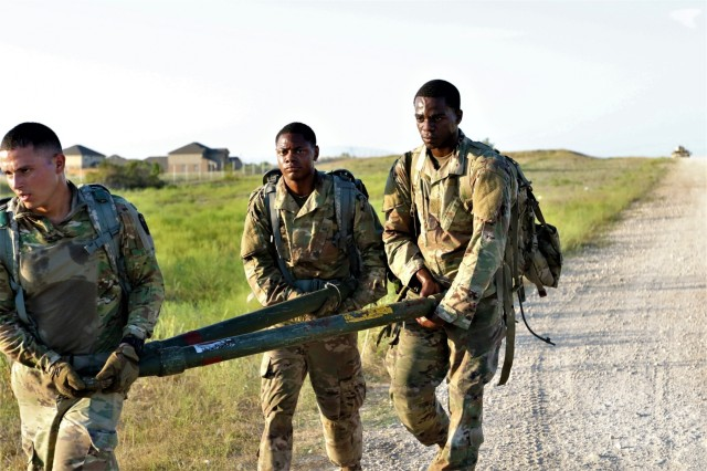 Sgt. Omar Gutierrez, Spc. Tyrik Brown, and Spc. Tyriek  Atkins, Headquarters and Headquarters Detachment, 163rd Military Intelligence Battalion, 504th Military Intelligence Brigade, carry a tow-bar, Sep. 6, 2019, Fort Hood, Texas. The team had to ruck march over a half a mile while carrying the tow-bar as a team. (U.S. Army photo by Sgt. Melissa N. Lessard)