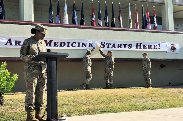 Maj. Gen. Patrick Sargent, Commanding General, and Command Sgt. Maj. William O'Neal unveil the re-designated U.S. Army Medical Center of Excellence (MEDCoE) lettering on the school house building during a re-designation ceremony on September 16, at Joint Base Sam Houston, Texas. (U.S. Army Image by Wesley Elliott, MEDCOM/OTSG)