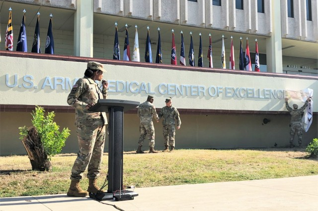 Maj. Gen. Patrick Sargent, Commanding General, and Command Sgt. Maj. William O'Neal shake hands after unveiling the re-designated U.S. Army Medical Center of Excellence (MEDCoE) lettering on the school house building during a re-designation ceremony on September 16, at Joint Base Sam Houston, Texas. (U.S. Army Image by Wesley Elliott, MEDCOM/OTSG)