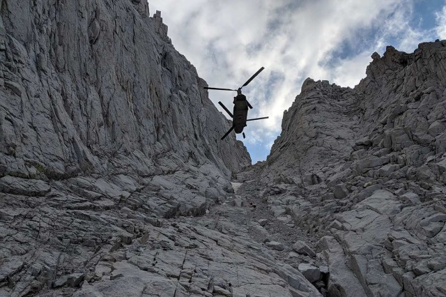 A U.S. Army CH-47F Chinook helicopter with the California Army National Guard, hovers as an injured hiker is hoisted on a litter from an area 13,800 feet up Mount Whitney in Inyo County, California, Aug. 25, 2019. The Chinook inserted a team from Inyo County Search and Rescue who provided aid to the woman and helped with her hoist rescue into the helicopter. The California Guard assists local, state and federal agencies during search and rescue missions and domestic disaster response efforts.