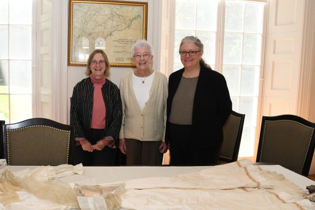 Marjorie Nelson Smart (center) brought an assortment of vintage garments worn by her family members and a collection of photos to show Dr. Laurie Rush (left) and the Fort Drum Cultural Resources staff while visiting LeRay Mansion with her daughter Cheryl (right) on Sept. 16. Smart is a distant relative of former owners of the mansion, and she never had the chance to see the entire mansion before now. Part of her collection will be available for viewing during the Fall History Tour on Sept. 28. (Photo by Mike Strasser, Fort Drum Garrison Public Affairs)