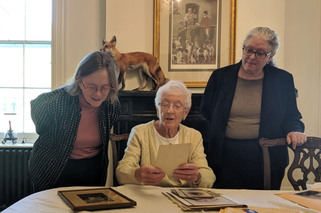 Marjorie Nelson Smart (center) and her daughter Cheryl Smart (right) show historic family photos to Dr. Laurie Rush (left), Fort Drum Cultural Resources manager, during a visit to LeRay Mansion on Sept. 16. Smart also brought a collection of garments and asked Rush if she could find an appropriate use for them as historical items. Part of her collection will be available for viewing during the Fall History Tour on Sept. 28.  (Photo by Mike Strasser, Fort Drum Garrison Public Affairs)