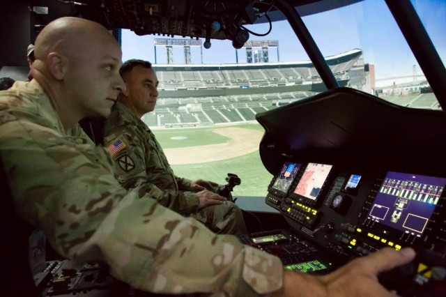 Capt. Justin Stewart, a USAARL pilot, gives Master Sgt. Kenneth Carey, USAARL's Chief Medical Laboratory Non-Commissioned Officer, a CAPT-E-VCS tutorial. The images displayed on the projection dome are of an urban flight environment in San Francisco, Calif.
