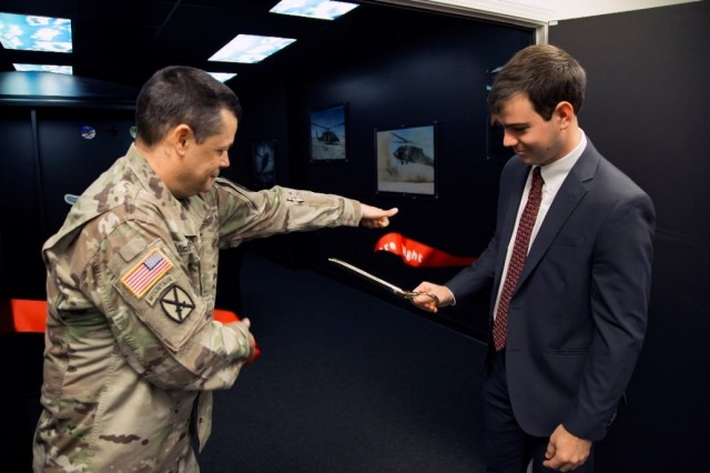 USAARL Commander, Col. Mark McPherson, assists Joshua DuPont, an aerospace engineer at CCDC S3I, with the ribbon cutting that unveiled the Laboratory's new state-of-the-art aviation research capability, the CAPT-E-VCS.
