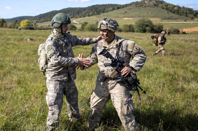 A Turkish soldier shakes hands with a U.S. soldier after parachuting in a joint airborne assault at Hohenfels training area during Saber Junction at the U.S. Army's Joint Multinational Readiness Center in Hohenfels, Germany, Sept. 18, 2019. Saber Junction 19 helps promote interoperability with participating allies and partner nations.