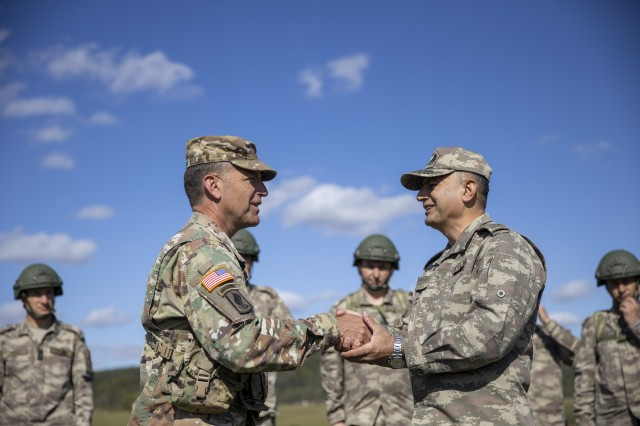 U.S. Army Maj. Gen. Andrew Rohling, the U.S. Army Europe deputy commanding general, and Turkish Brig. Gen. Özgür Nuhut, the 14 Mechanized Infantry Brigade commander shake hands after congratulating paratroopers on a successful jump during Saber Junction 19. Saber Junction 19 helps promote interoperability with participating allies and partner nations.