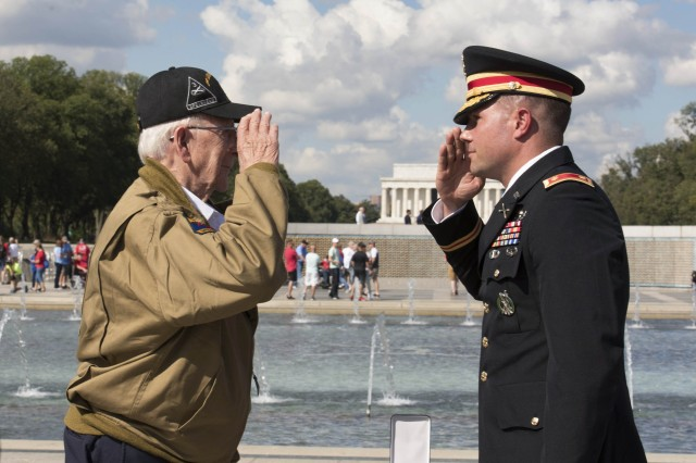 Army Maj. Peter Semanoff salutes World War II veteran Clarence Smoyer after awarding him the Bronze Star during a ceremony at the National World War II Memorial in Washington, Sept. 18, 2019.