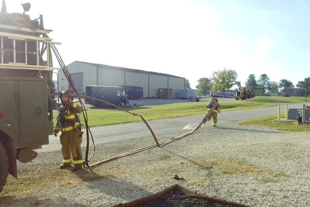 Firefighters with the Indiana National Guard's 1019th Engineer Detachment pull a fire hose as quickly as they can from a fire engine during training at Muscatatuck Urban Training Center in Butlerville, Ind., on Sep. 17.