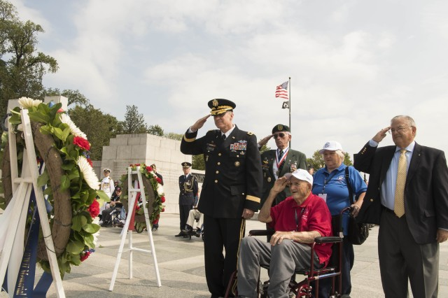 Maj. Gen. Mark C. Schwartz, a special assistant in the Office of the Director of the Army Staff, and World War II veteran James Washburn salute a commemorative wreath during the Operation Market Garden and Battle of Angaur 75th Anniversary Commemoration at the National World War II Memorial in Washington, Sept. 17, 2019.