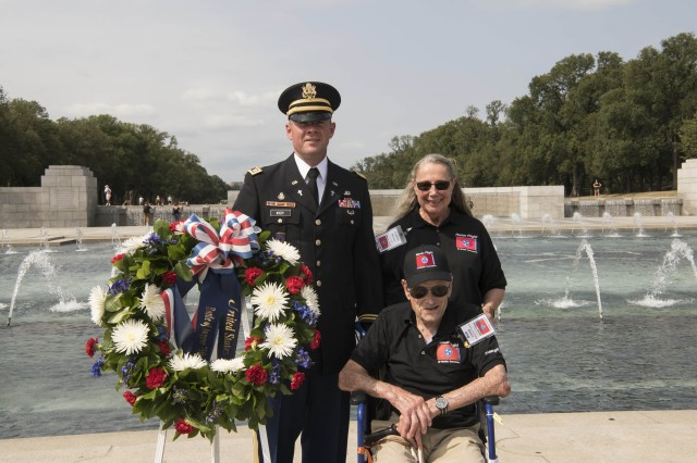 Army Chaplain (Capt.) Russell Woody; World War II veteran Bob Lucas of Middle, Tenn.; and Jeanne Wood, an Honor Flight guardian, pose with a commemorative wreath they placed during the Operation Market Garden and Battle of Angaur 75th Anniversary Commemoration at the National World War II Memorial in Washington, Sept. 17, 2019.