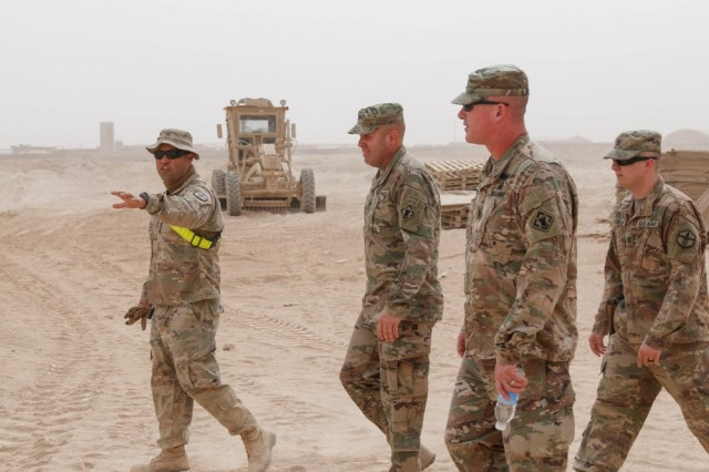 Sgt. Armando Lopez, left, assigned to 387th Engineer Company, 315th Engineer Battalion, 301st Maneuver Enhancement Brigade, briefs an overview of an ammunition holding area expansion project at Al Asad Air Base, Iraq, to Col. Patrick Sullivan and Command Sgt. Maj. John Brennan, commander and sergeant major, respectively, of 20th Engineer Brigade, during their battlefield circulation Oct. 10, 2018.