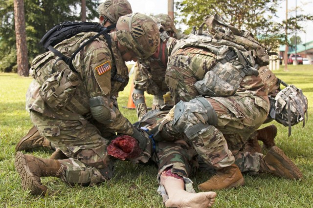 Soldiers from across the 3rd Infantry Division prepare a simulated casualty for extraction, by placing a tourniquet on its upper right leg during a Medical Simulation Mannequin customer test for the recently upgraded mannequins, Sept. 10, 2019, at Fort Stewart, Georgia. The purpose of this event is to assess the functionality and usability of medical simulation mannequins in support of the Soldier mission in and out of an operational environment. (U.S. Army photo by Sgt. Arjenis Nunez/Released)
