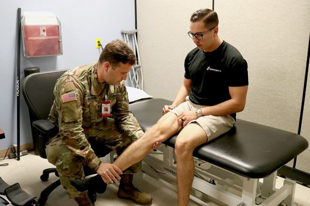 1st Lt. Nicholas Wankum, a physical therapist, evaluates the progress Marine Staff Sgt. Dalton Everhart has made in his range of motion since the recruiter came to the emergency department after an injury nearly a month before this Sept. 13 appointment at Madigan Army Medical Center.