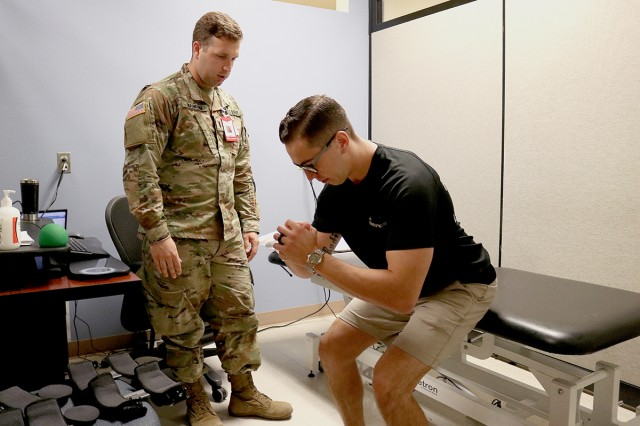 1st Lt. Nicholas Wankum, a physical therapist, watches as Marine Staff Sgt. Dalton Everhart performs a squat, which the recruiter couldn't do when he first came to the emergency department after an injury nearly a month before this Sept. 13 appointment at Madigan Army Medical Center.