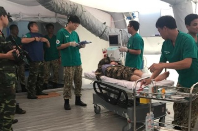 Military members from Military Hospital 103 run emergency patient scenarios during the level II hospital field training exercise and training validation June 22, in Hanoi, Vietnam.