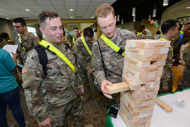 """A Soldier slowly pulls out a wooden block from a tower labeled with """"Together Working For Change."""""""
