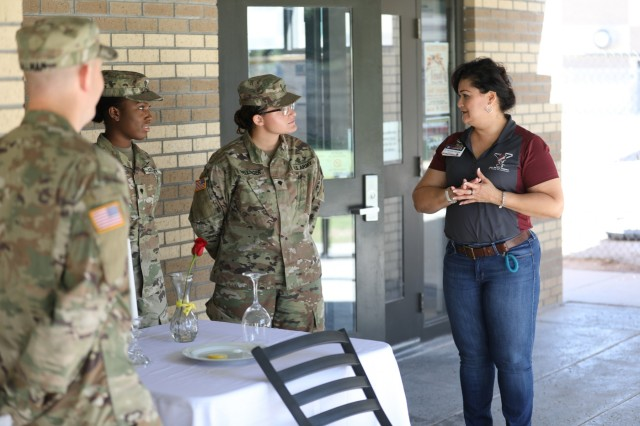"""EL PASO, Texas -- A culinary team, assigned to 4th Battalion, 6th Infantry Regiment, 3rd Armored Brigade Combat Team """"Bulldog"""", 1st Armored Division, constructed a Fallen Comrade Table, used as a symbol in military dining facilities and dining-in events to honor fallen and missing comrades, and spoke to the symbolism of each piece of the place of honor to students and faculty at Rio Bravo Middle School in El Paso, Texas, Sept. 20. The United States Congress passed a resolution authorizing National POW/MIA Recognition Day to be observed on July 18, 1979 and from 1986 onward the date moved to the third Friday of September. (U.S. Army photo by Sgt. Alon J. Humphrey, 3rd ABCT, 1st AD Public Affairs Office)"""