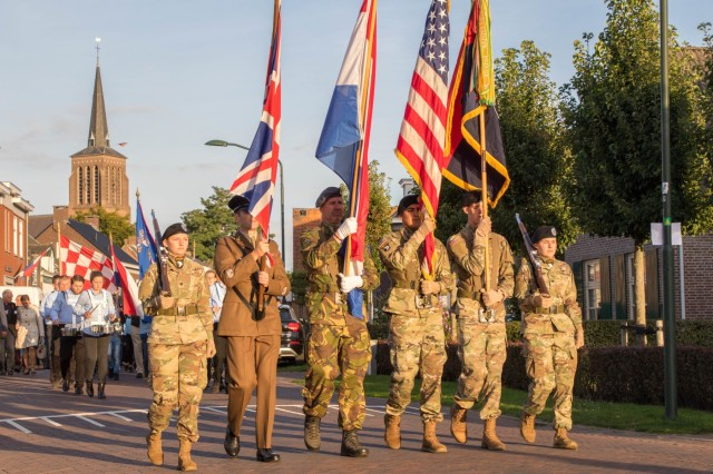 Members of the 101st Airborne Division's color guard, along with members of the British and Dutch military, lead the formation headed for the Eerde Windmill to kick off the Liberation of Eerde Commemoration, September 17, 2019, at Eerde, the Netherlands. This year marks the 75th anniversary of Operation Market Garden in the Netherlands. Commemorations honoring the Allied soldiers who participated in the historic airborne operation which liberated several Dutch towns take place Sept. 14-22, 2019. (U.S. Army photo by Pfc. Michael Ybarra)