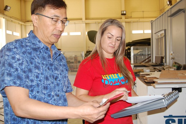 Edison Gomez, Far East Division chief, and Electronics Mechanic Leader Valerie Hurd confirm parts for the AN/TRC-170 Tropospheric Scatter Microwave Radio Terminal are in a shipment of supplies.