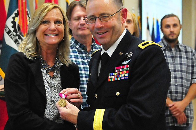 Kelli Whitesides, U.S. Army Sustainment Command, receives the Superior Civilian Service Medal from Brig. Gen. Troy Galloway, deputy commanding general for  operations, First U.S. Army, during the retirement ceremony Sept. 19 at Rock Island Arsenal, Illinois. (Photo by Jon Micheal Connor, ASC Public Affairs)