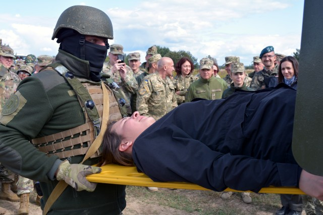 Ukrainian Soldiers demonstrate how to load an injured person into an ambulance at the Joint Multinational Training Group Ukraine in Yavoriv, Ukraine.  The demonstration was part of Exercise Rapid Trident and observed by those attending the 27th annual Multinational Military Medical Engagement, hosted by Regional Health Command Europe.