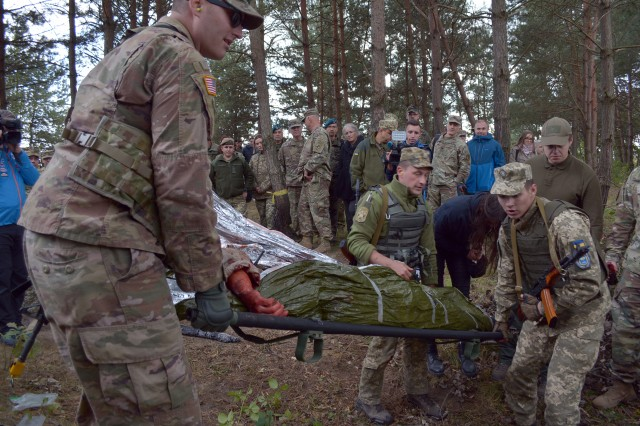 U.S. and Ukrainian Soldiers work together to demonstrate evacuating an injured Soldier from the battlefield at the Joint Multinational Training Group Ukraine in Yavoriv, Ukraine.  The demonstration was part of Exercise Rapid Trident and observed by those attending the 27th annual Multinational Military Medical Engagement, hosted by Regional Health Command Europe.