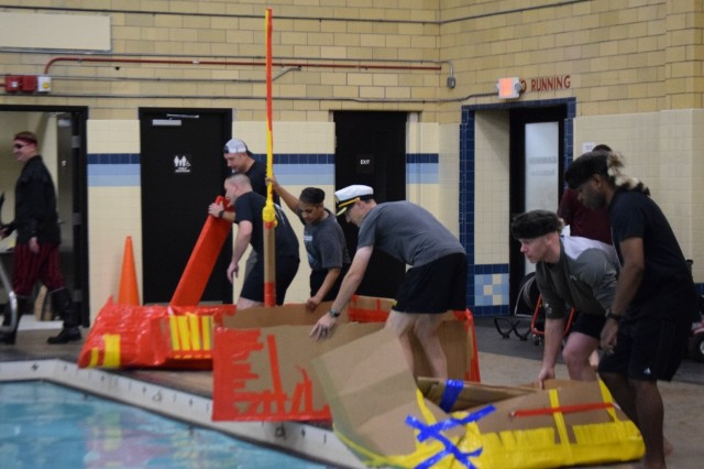 """Battalion command teams prepare to put their boats in the pool for the """"Boat Wars"""" competition at Gammon Physical Fitness Center, Fort Knox, Kentucky, Sept. 22. The """"Boat War"""" was a team building exercise that leadership teams participated in during the 3rd Recruiting Brigade's three-day training forum."""