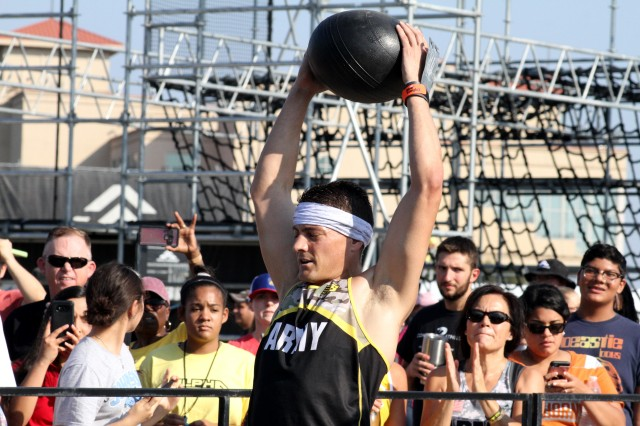 Army Lt. Col. Eric Palicia holds a medicine ball over his head during a strength challenge at the 2019 Alpha Warrior Inter-Service Battle, while a crowd cheers him on at Retama Park, Selma, Texas, Sept. 14, 2019. In its second year, the battle brought together teams from the Air Force, Navy and Army to determine service champions. The Air Force won the first battle last year and successfully defended its crown, winning again in 2019.