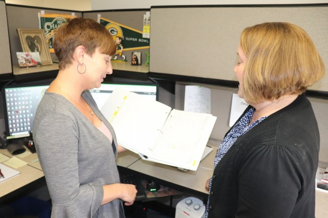 Procurement Analyst Katie Opper and Business Operations Division Chief Lynn Herrman, both with Mission Installation Contracting Command (MICC)-Fort McCoy, discuss a project Aug. 22, 2019, at the MICC-Fort McCoy building at Fort McCoy, Wis. MICC-Fort McCoy supports the garrison as well as the post's tenant organizations with the solicitation and awarding of contracts for supplies, services, and construction. (U.S. Army Photo by Scott T. Sturkol, Public Affairs Office, Fort McCoy, Wis.)