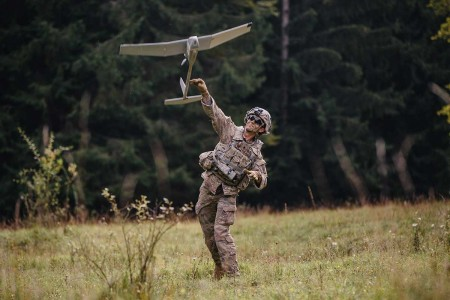 A U.S. Army paratrooper assigned to 503rd Infantry Regiment, 173rd Airborne Brigade, throws a small unmanned aircraft system Raven into flight prior to expected enemy contact in Hohenfels Training Area, Germany, during Saber Junction 19, Sept. 22, 2019. Forward observers who double as unmanned aircraft system operators can utilize equipment like the Raven to observe enemy targets from a safer distance and different perspective. S