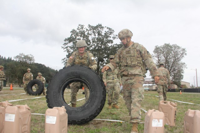 Soldiers tackle flipping an approximately 220 pound LMVT tire prior to the marksmanship challenge of the Army's CSM Jack L. Clark Jr. Army Best Medic Competition,hosted by the U.S. Army Medical Command, at Joint Base Lewis-McChord, Washington, Sept. 24-27, 2019.Twenty-seven two-Soldier teams from all around the world traveled to Washington state to compete in the finals to be named the Army's Best Medic. The competition is a 72-hour arduous test of the teams' physical and mental skills. Competitors must be agile, adaptive leaders who demonstrate mature judgement while testing collective team skills in areas of physical fitness, tactical marksmanship, leadership, warrior skills, land navigation and overall knowledge of medical, technical and tactical proficiencies through a series of hands-on tasks in a simulated operational environment.
