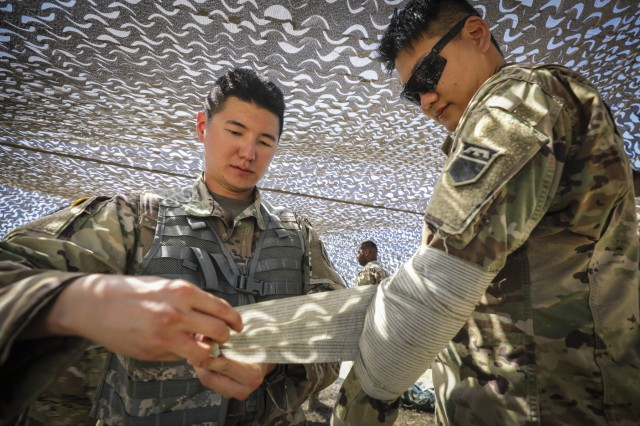 Army Reserve Spc. Jong Lin (left), a motor vehicle operator and native of Downey, California, assigned to the 453rd Chemical Battalion, 209th Regional Support Group, 76th Operational Support Command, applies a pressure dressing to Army Reserve Private 1st Class Seung Kim, a wheeled-vehicle mechanic and native of Irvine, California, assigned to Headquarters and Headquarters Company, 453rd Chem. Bn., 209th RSG, at Los Alamitos, Calif. during a brigade wide Field Training Exercise, Sept. 13. The exercise involved more than 2000 Army Reserve Soldiers, four battalions and 15 companies conducting a variety of training simultaneously at locations across the nation.