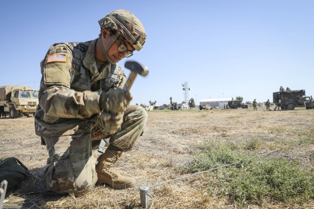 An Army Reserve Soldier from the 307th Chemical Company, 209th Regional Support Group, 76th Operational Response Command, hammers Biological Integrated Detection System (BIDS) grounding stakes into the dirt at Los Alamitos, Calif., Sept. 13, during a four-day brigade wide Field Training Exercise.  The exercise involved more than 2000 Army Reserve Soldiers, four battalions and 15 companies conducting a variety of training simultaneously at locations across the nation as part of an ambitious brigade level field training exercise (FTX) hosted by the 209th Regional Support Group, 76th Operational Response Command.