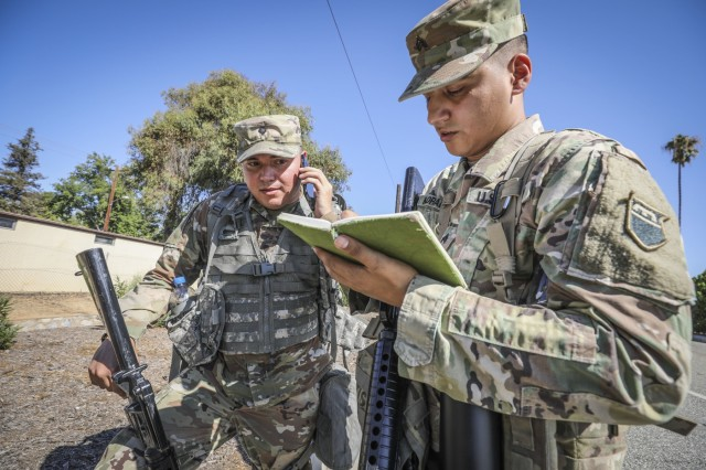 """Army Reserve Spc. Jamison Kelley (left), a chemical, biological, radiological and nuclear specialist and native of Apple Valley, California, assigned to the 374th Chemical Company, 453rd Chemical Battalion, 209th Regional Support Group, 76th Operational Response Command, calls in a situation report to his higher command, while Army Reserve Sgt. Antonio Morales, squad leader and native of Riverside, Calif., assigned to the 374th Chem. Co., 453rd Chem. Bn., makes notes after their squad encountered """"enemy"""" resistance during a patrol at March Air Reserve Base, September 14. The training was part of a four-day brigade wide Field Training Exercise involving more than 2000 Army Reserve Soldiers, four battalions and 15 companies conducting a variety of training simultaneously at locations across the nation."""