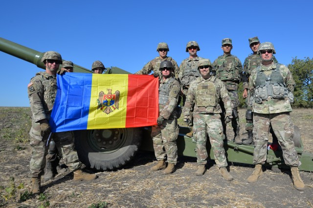 North Carolina (NCNG) and Alabama National Guard (ALNG) Soldiers holding a Moldovan flag pose with Moldovan soldiers at Operation Fire Shield 2019 hosted by Moldova, Sept. 19 at Bulboaca Training Area, Moldova. Fire Shield's mission is sharing knowledge and best practices between the NCNG and ALNG artillery experts, Moldovan soldiers and officers and other nations attending the annual event. The NCNG has teamed with Moldova for more than two decades via the State Partnership Program designed to increase peace and stability across Europe.
