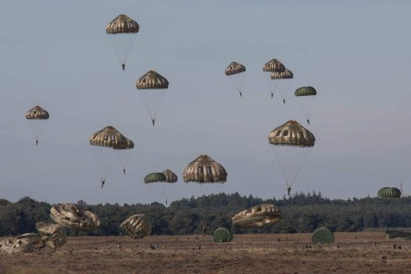 A group of U.S. Army and international paratroopers parachute out of a C-130 aircraft onto Ginkelse Heide Drop Zone during the 75th Anniversary of Market Garden at Arnhem, Netherlands, Sept. 20, 2019. These paratroopers are honoring the memories of service members from all allied nations that participated in the jump in September 1944, as part of Operation Market Garden, the largest airborne operation in the history of warfare.