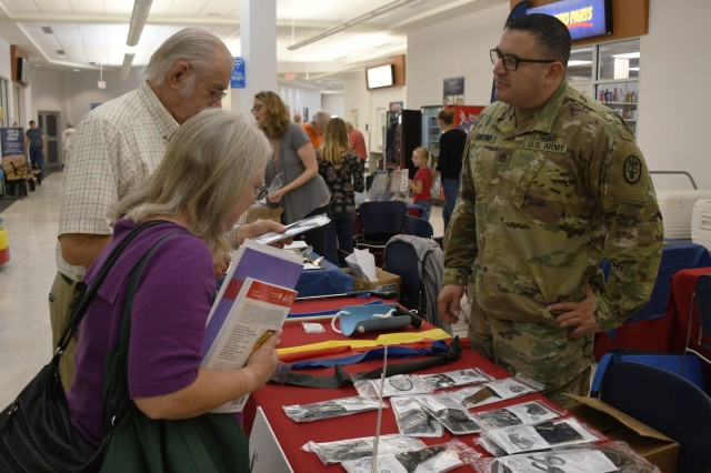 FORT DRUM, N.Y. -   Staff Sgt. Osuna Castro (right), the noncommissioned officer in charge of the Fort Drum Occupational Therapy Clinic, discusses adaptive equipment and intervention techniques designed to increase functional independence with attendees of the annual Fort Drum Retiree Application Day at the Fort Drum Exchange Sept. 21.  Multiple healthcare representatives from the U.S. Army Medical Department Activity, Fort Drum, were in attendance at the event to provide retirees and their families with valuable health and wellness information.  (Photo by Warren W. Wright Jr., Fort Drum MEDDAC Public Affairs)