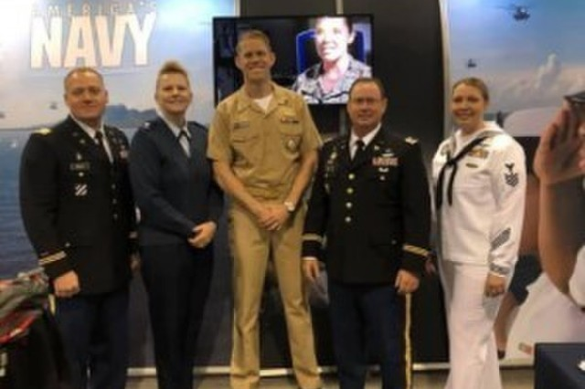 Maj. Sloan Kelly and Lt. Col. Lee Clark at at a military recruiting booth at the 2019 American Academy of Physician Assistants Conference in Denver, Colorado.