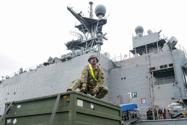 Specialist Zachary Verbruggen, assigned to the 109th Transportation Company, 17th Combat Support Sustainment Battalion, U.S. Army Alaska, yells to fellow Soldiers while securing U.S. Marine Corps bulk fuel supplies and equipment from the U.S.S. Comstock (LSD-45), a Whidbey Island-class dock landing ship, on an M872 trailer at the port of Seward, Alaska, Sept. 19, 2019, for transport to Joint Base Elmendorf-Richardson, Alaska. The U.S. Navy is conducting an Arctic Expeditionary Capabilities Exercise to test its logistical effectiveness and joint-service interoperability while responding to conflict or disaster in an austere environment with no organic assets.